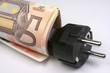 Billetes de euro enrollados en un enchufe