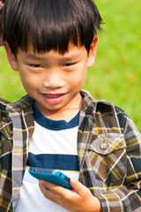 Asian little boy playing and calling Smart-phone