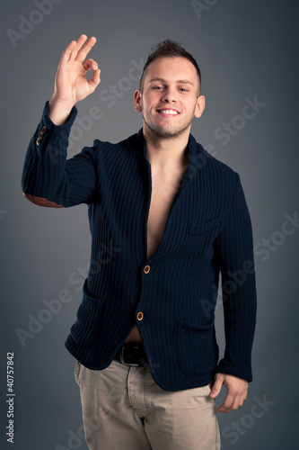 Happy casual man ok sign over grey background.
