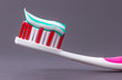 A pink toothbrush with toothpaste