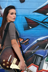 woman holding a guitar and posing in front of a graffiti wall