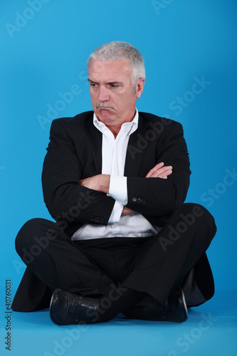 Grumpy man sitting on the floor
