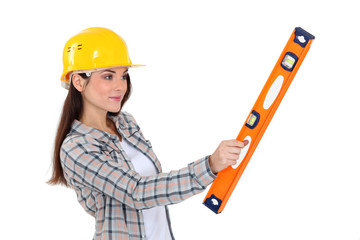 A female construction worker holding a level.