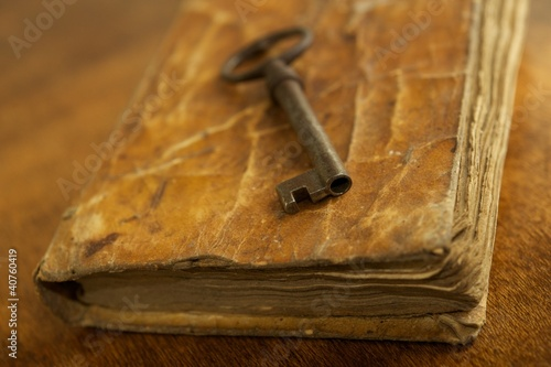 Old metal key on vintage book.