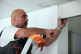 Worker putting a doorway in a partition wall