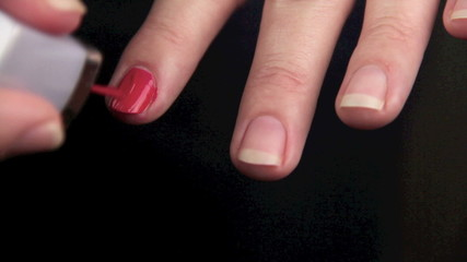 Female painting her finger nails with nail polish.
