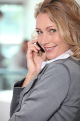 Blond businesswoman taking a call whilst stood in the office