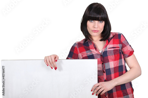 Woman with checkered shirt and white poster
