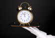 Hand in glove holding silver tray with alarm clock isolated