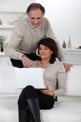 couple with laptop computer at home
