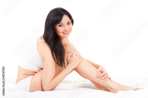 Cute woman sitting on the white bed