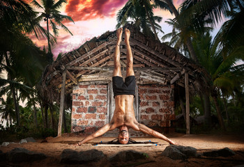 Yoga head stand pose near fisherman hut