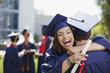 Smiling graduates hugging outdoors