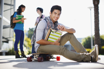 Student sitting on skateboard outdoors