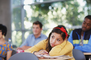 Student resting head on desk in classroom