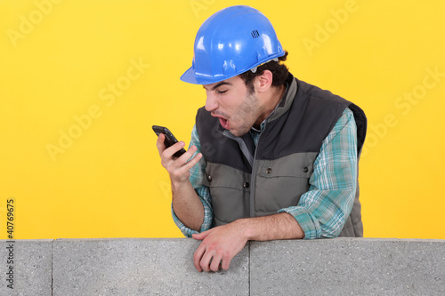 Man staring at his mobile phone in disbelief