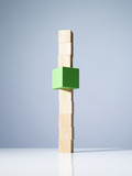 Green cube in stack of wooden cubes