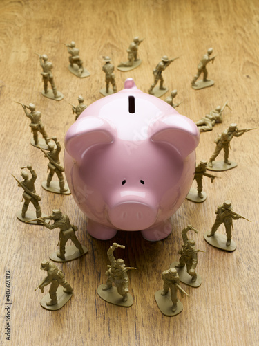 Toy army men surrounding piggy bank