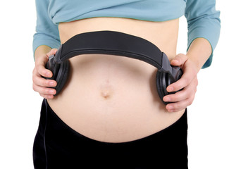 Headphones on a pregnant woman's abdomen