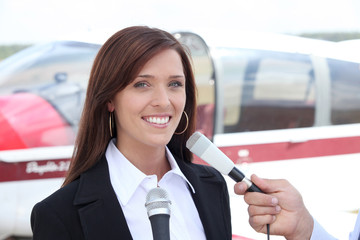Woman interviewed in front of airplane