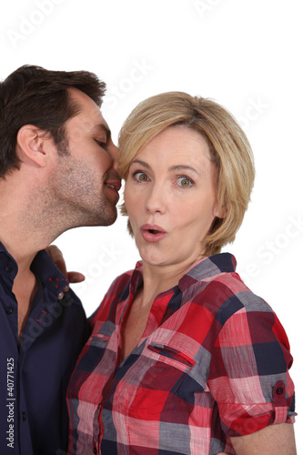 Man talking to woman's ear