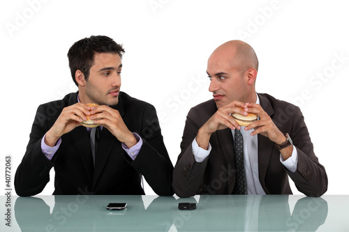 duo of businessmen eating hamburger