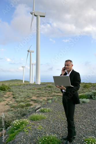 Businessman using a laptop on a windfarm