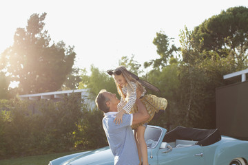 Father lifting daughter in air outdoors