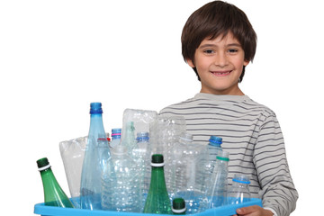 Little boy sorting plastic bottles for garbage