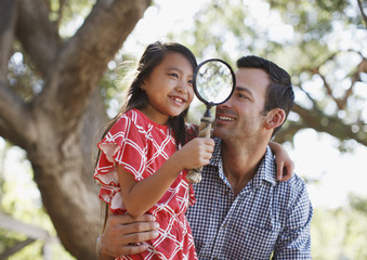 Father carrying daughter with magnifying glass