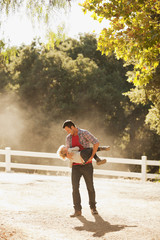 Father carrying son on dirt road