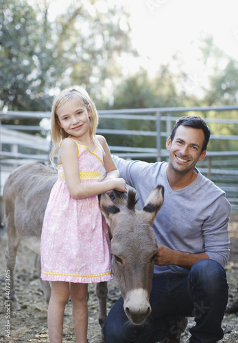 Father and daughter petting donkey