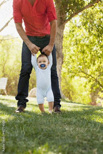 Father helping baby walk outdoors