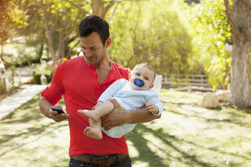 Father with baby using cell phone