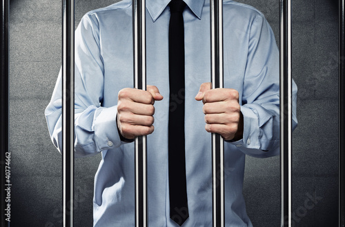 Young corrupted businessman behind the prison bars
