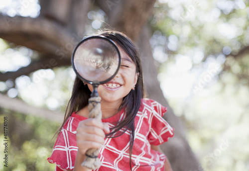 Girl using magnifying glass outdoors