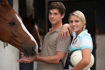 Young couple at a riding stable