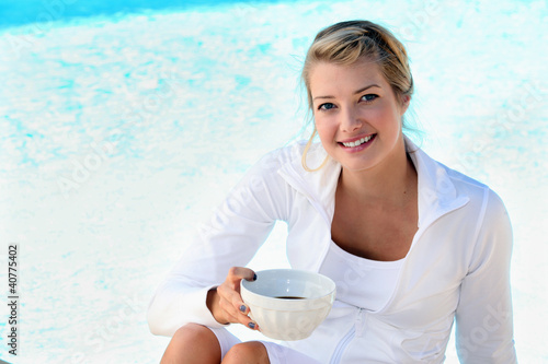 blonde sitting on the edge of swimming-pool