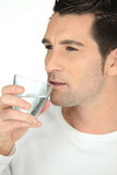 bust shot of man drinking glass of water