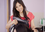 Cute young hairstylist with blow dryer poster