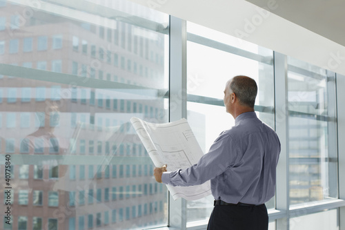 Businessman reading blueprint in office