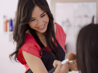 Cute young makeup artist applying makeup to a customer