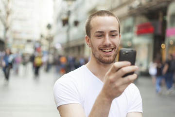 Young Man with cell phone walking