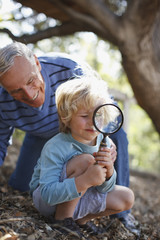 Older man and grandson using magnifying glass