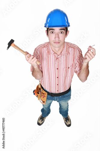 Tradesman holding a hammer and a nail
