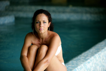 Brunette sat by the edge of the swimming pool