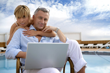 Couple using a laptop by the poolside