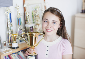 Smiling girl holding trophy in bedroom