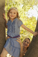Mother helping daughter climb tree