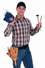 portrait of carpenter holding drill and hammer